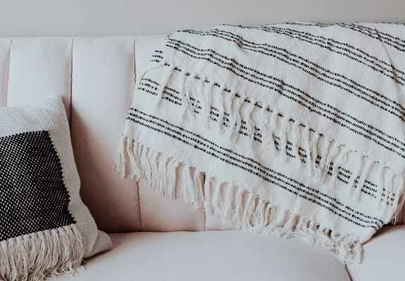 White couch with throw blanket and pillow