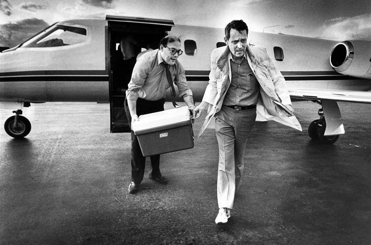 Dr. Starzl rushes from a plane carrying a liver in a cooler.