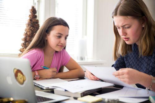 Två ungdomar läser läxor vid matbordet