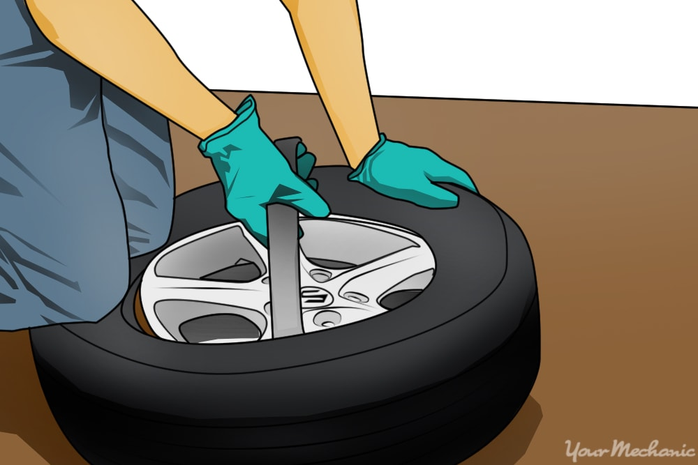 person installing wheel with tire iron