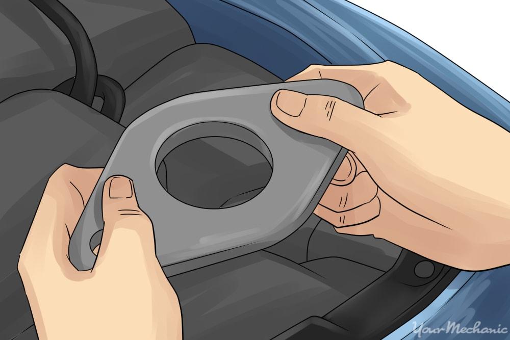 hand removing the carburetor gasket