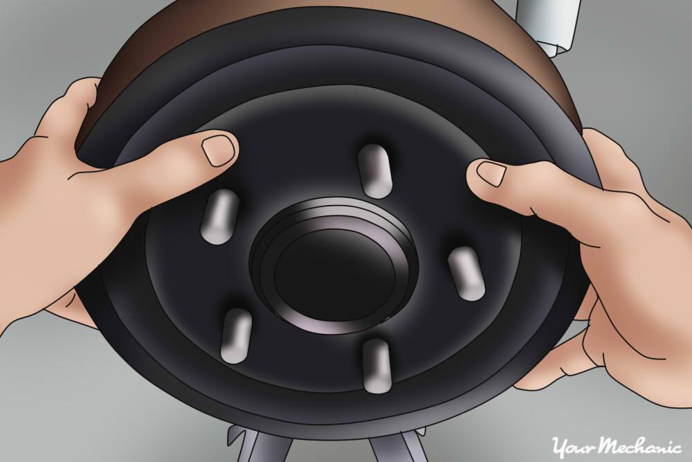 person sliding brake drum back on over the brake shoe