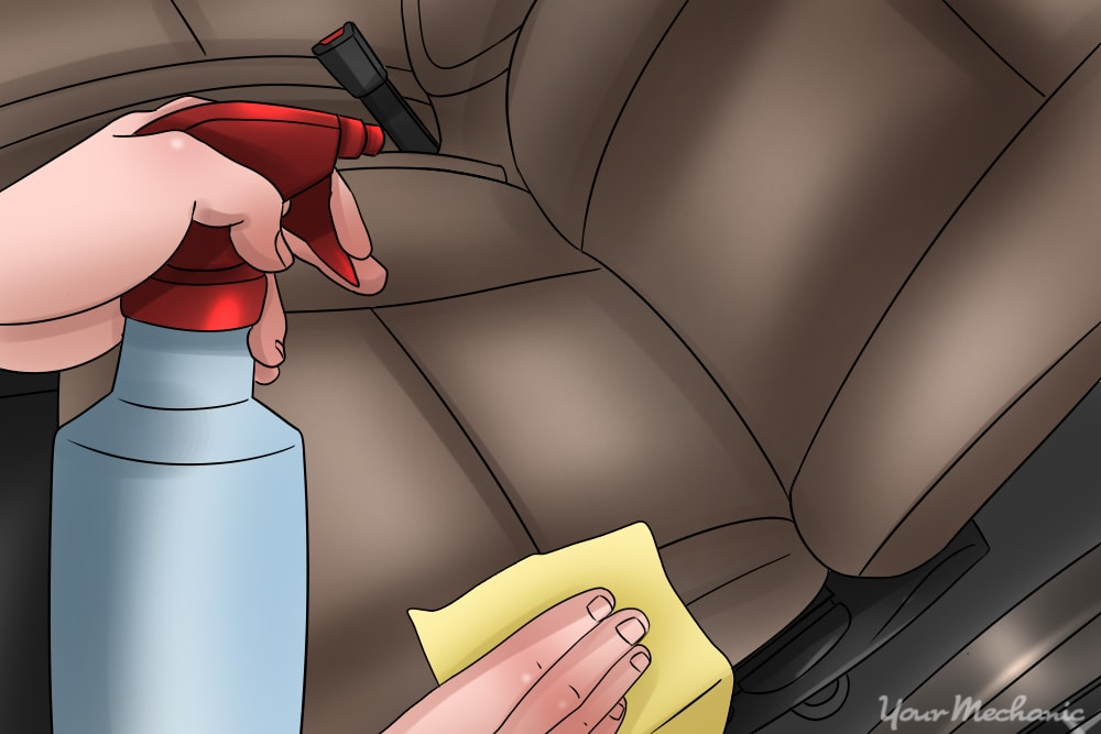 1 How to Get Rid of Grease Stains In a Car picture of a person spraying a bottle of water on a car seat and a white cloth in the other hand - How To Get Food Grease Stains Out Of Car Upholstery