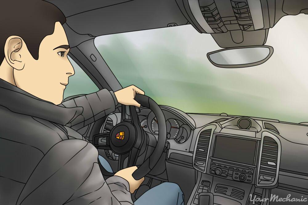 inside shot of person driving a porsche cayenne