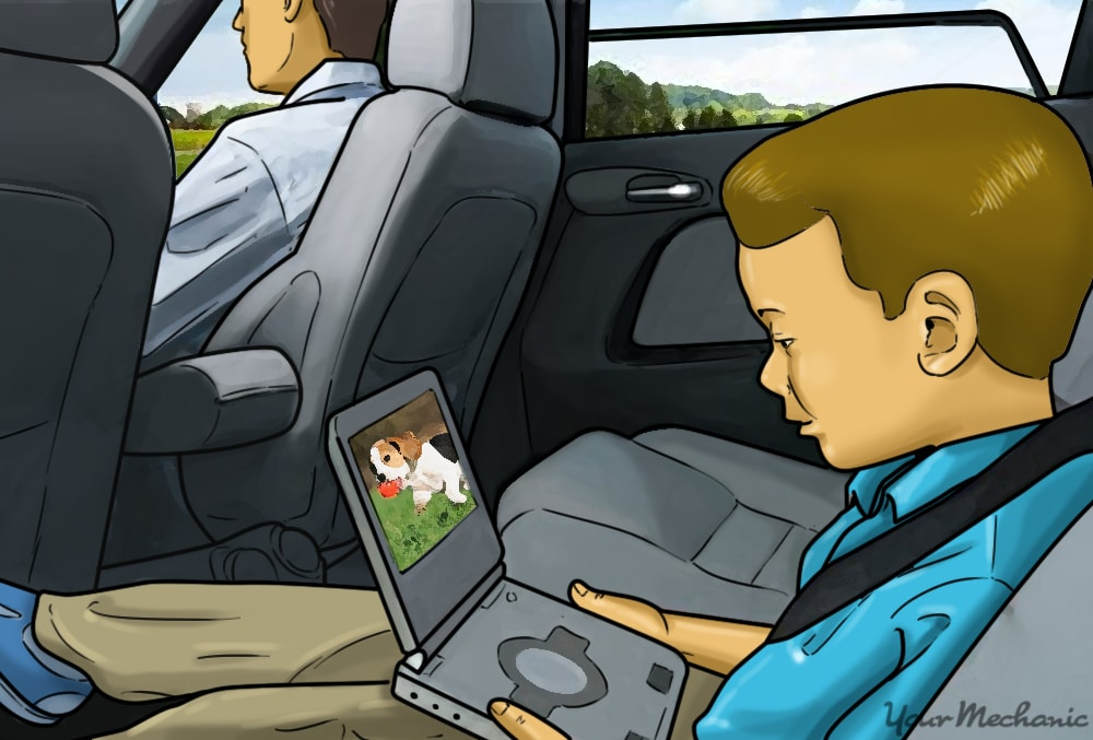 child sitting in back seat holding a dvd player
