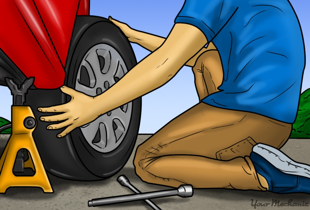 person replacing tire with spare