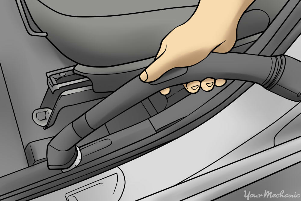person vacuuming upholstery of car