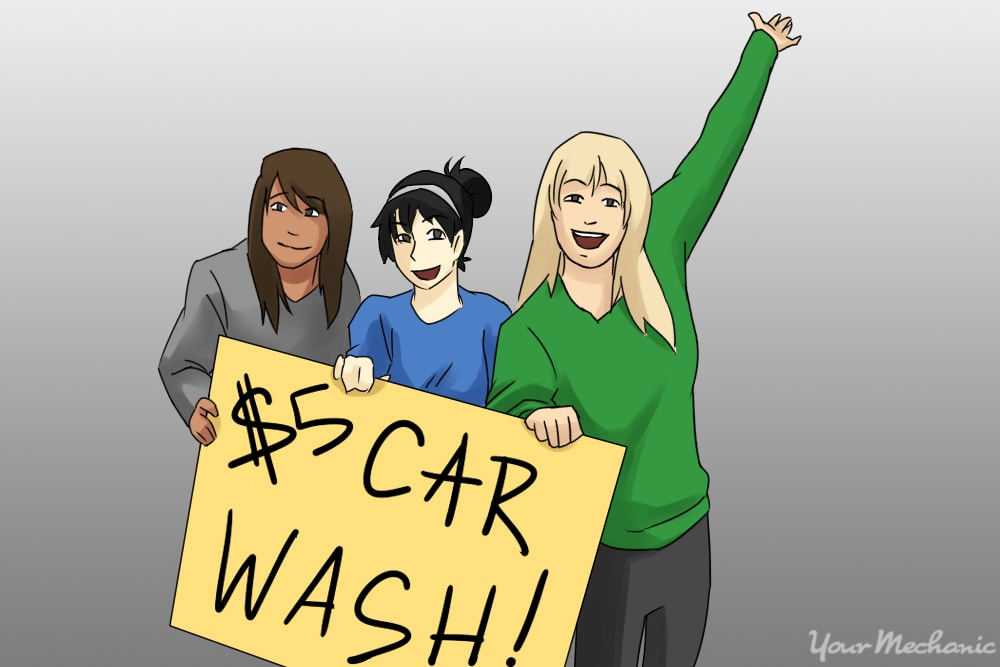 girls holding car wash sign