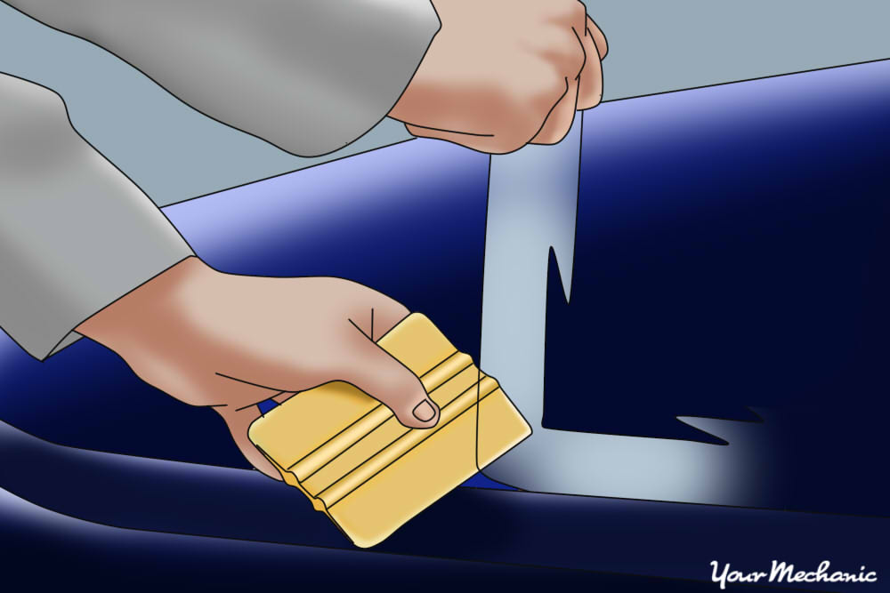 non metal scraper being used to remove film