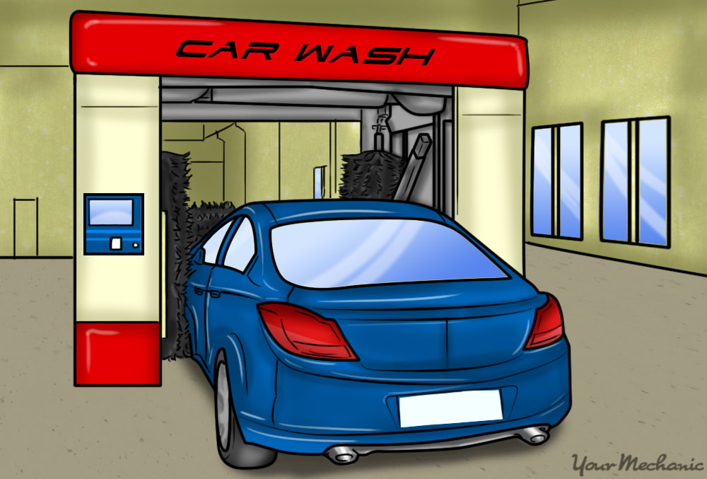 car parked in a carwash, large brushes surrounding it