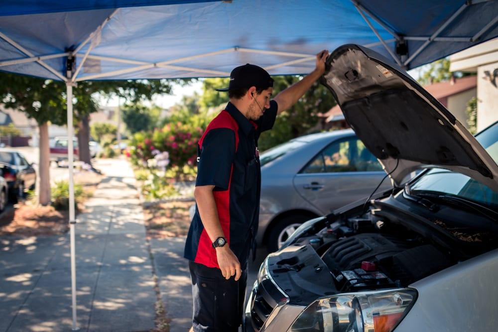 mechanic looking into car