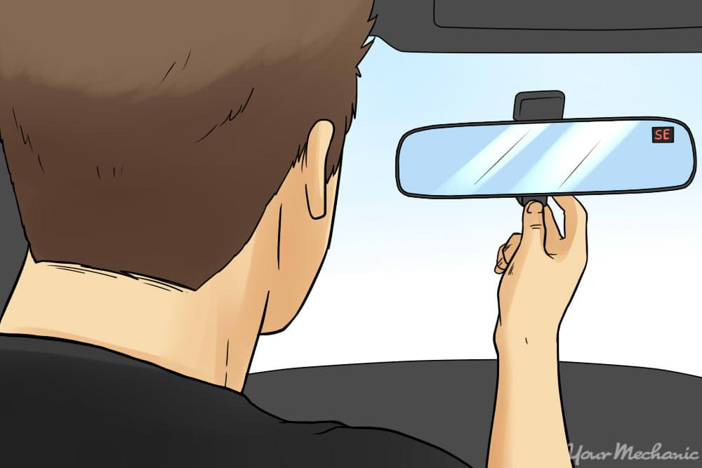 person looking into rearview mirror compass