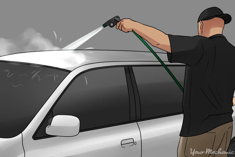 person rinsing down vehicle
