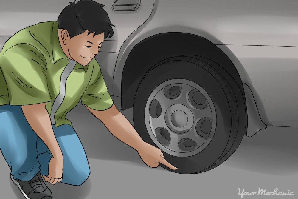 person crouched down inspecting tires