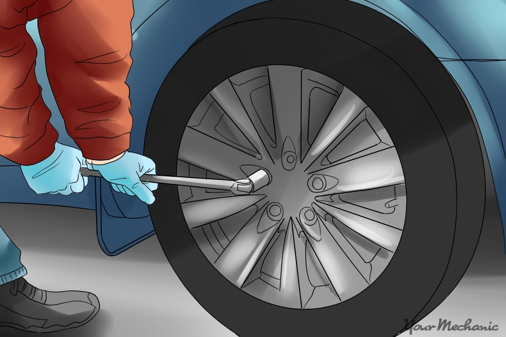 mechanic loosening a lug on a tire