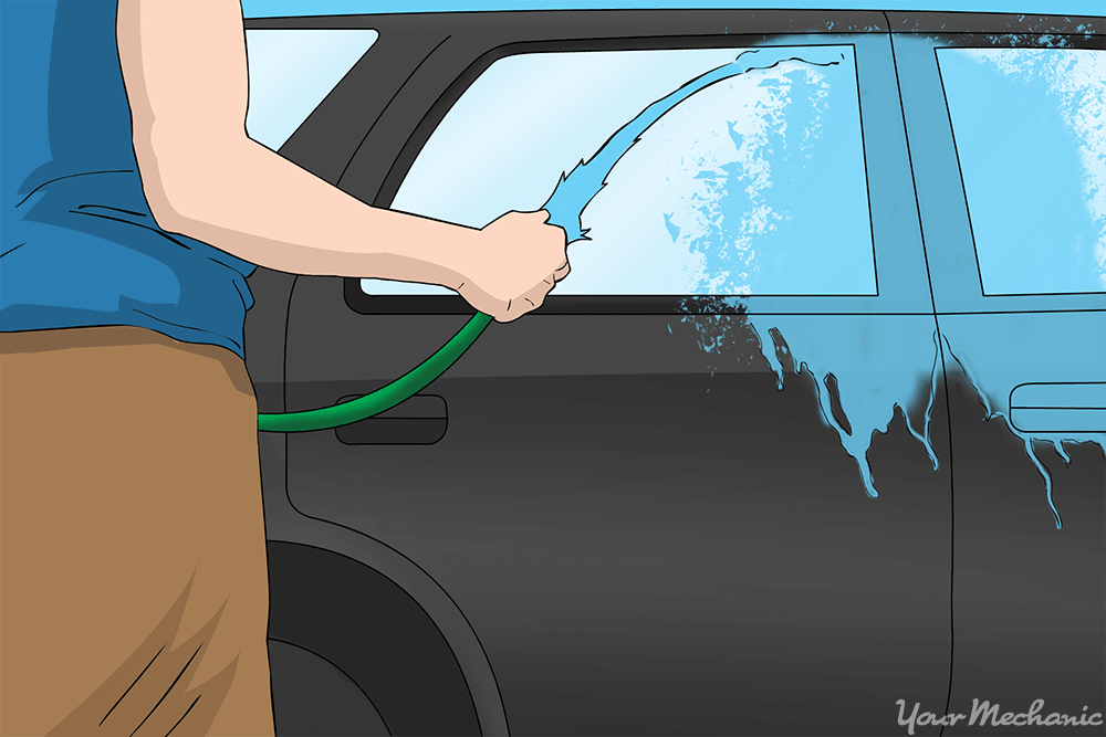 person rinsing car with hose