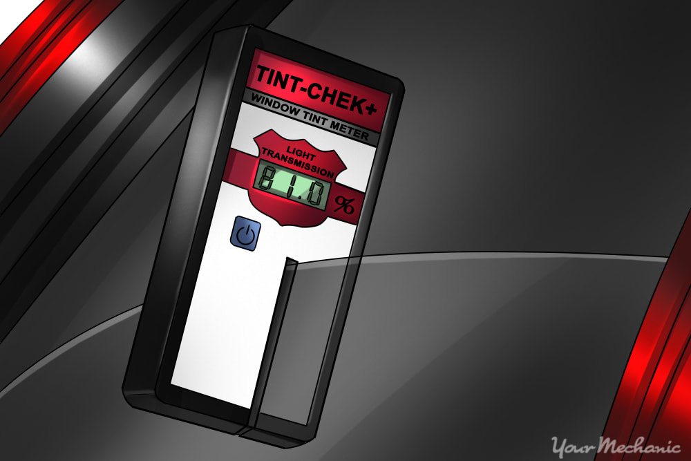 a window tint meter being used on a halfway closed driver side door window