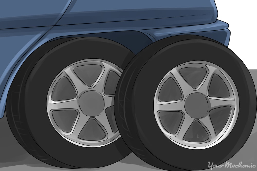 a used tire of the same size sitting next to a left rear tire already on a vehicle