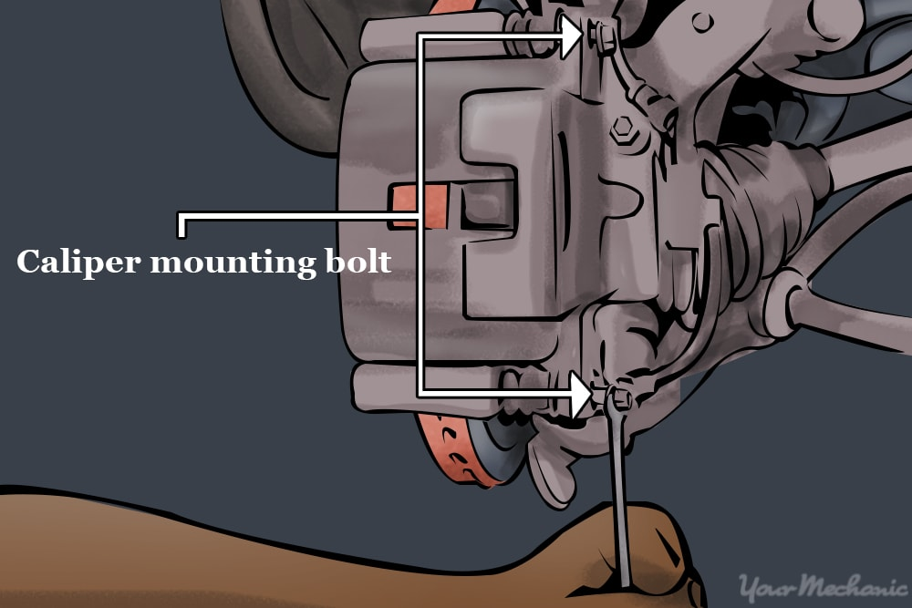 person removing caliper mounting bolts