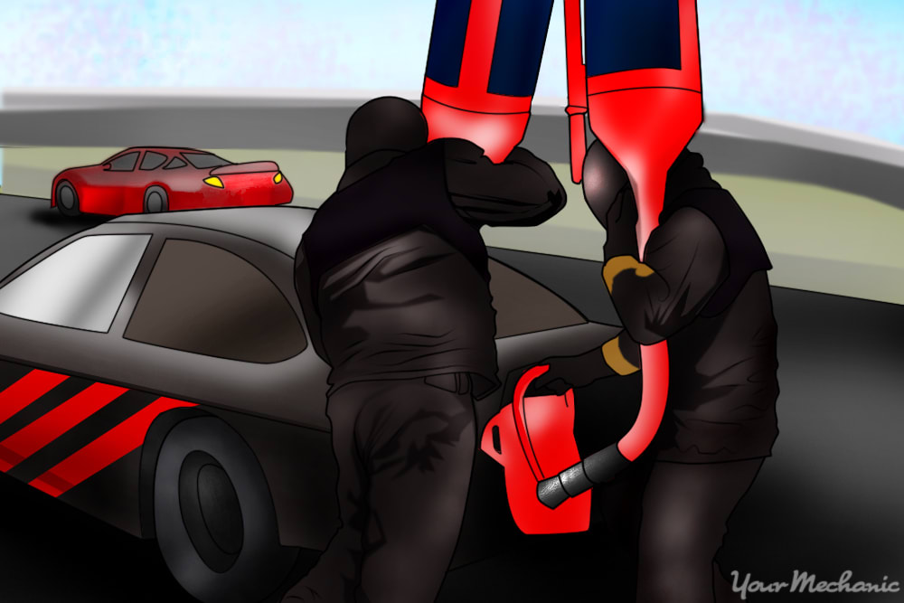 nascar gasman holding a gas can in place while refueling the car as the catch can man holds an empty fuel can