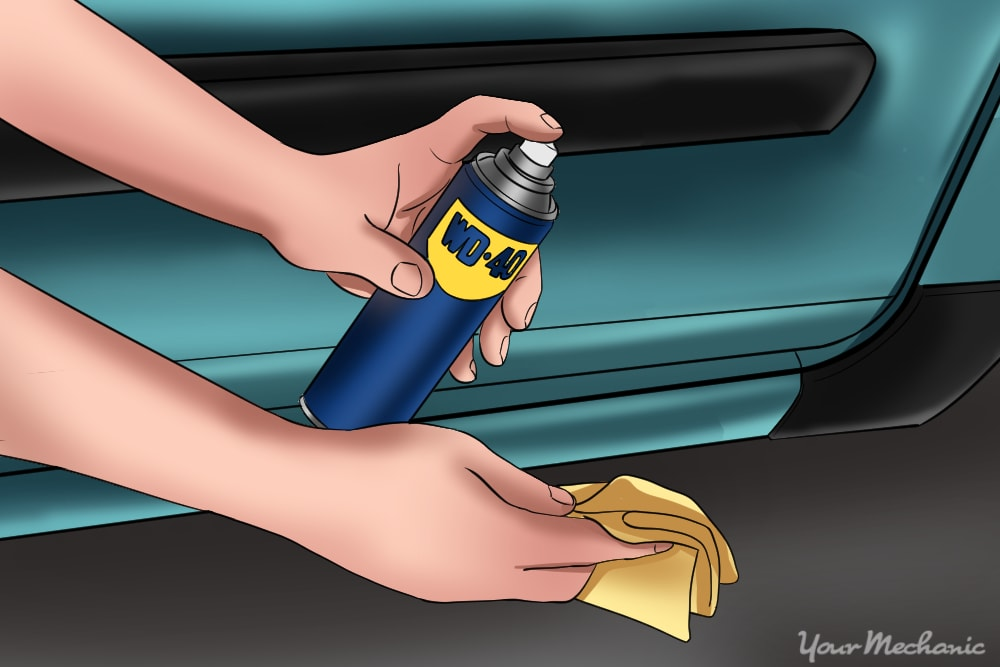 person holding wd-40 and rag in hand