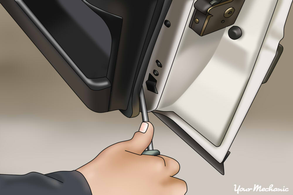 inside of a door panel being pryed with a screwdriver