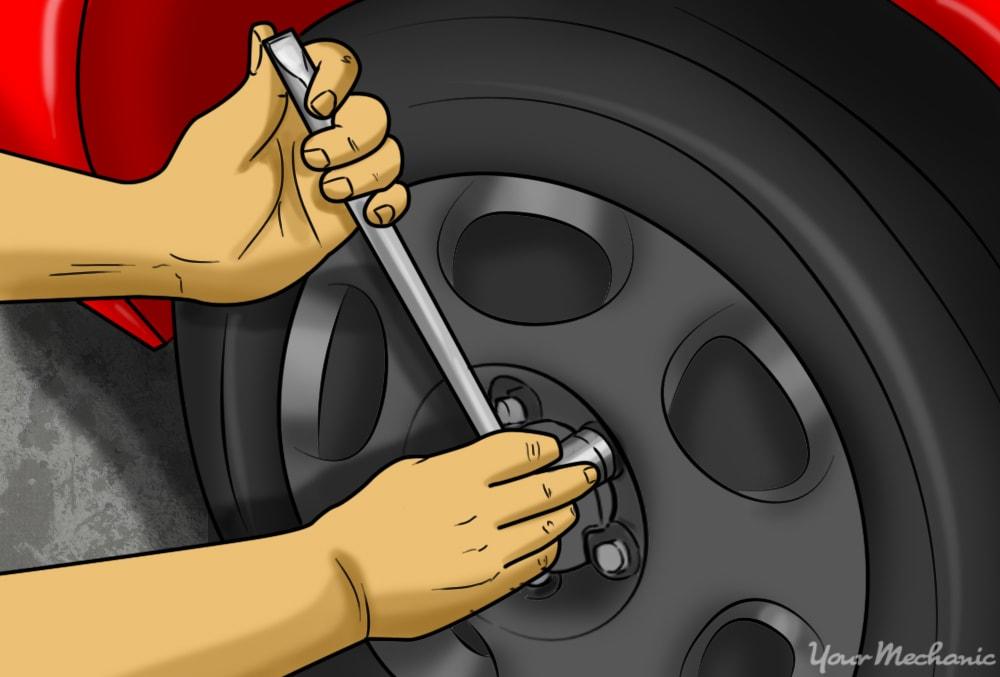 person tightening lug nuts