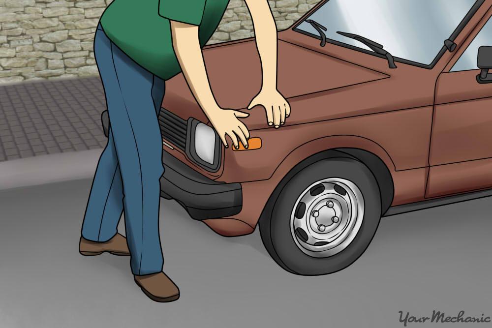 man pushing down hood of car