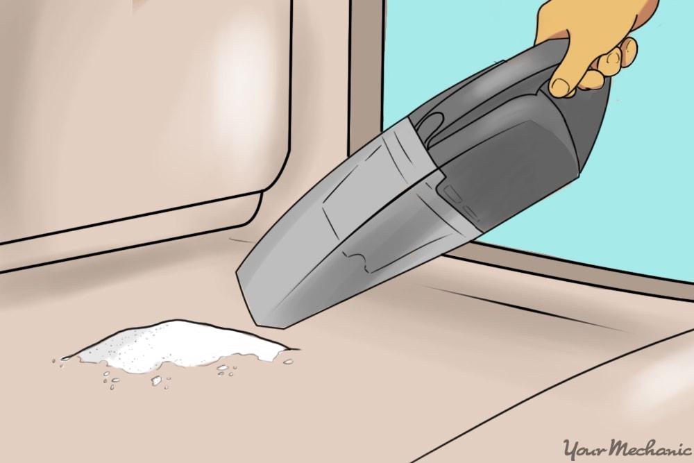 baking soda on car floor being vacuumed