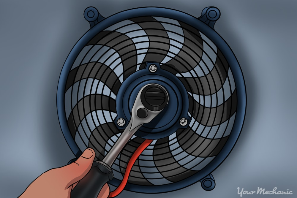 hand using ratchet removing retaining nut on cooling radiator fan blade
