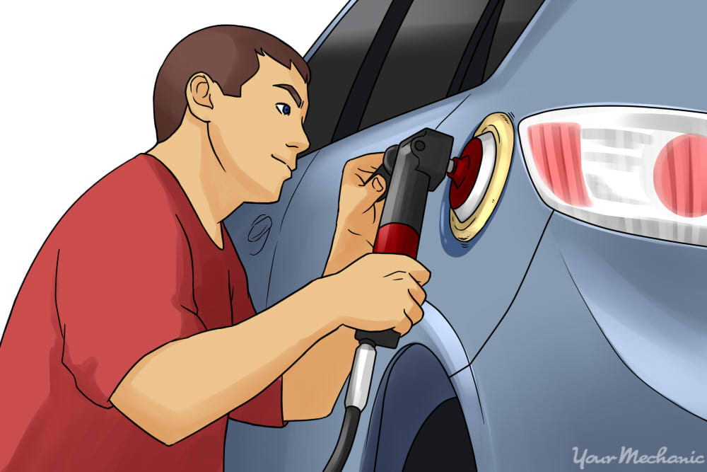 person buffing out car paying attention to detail