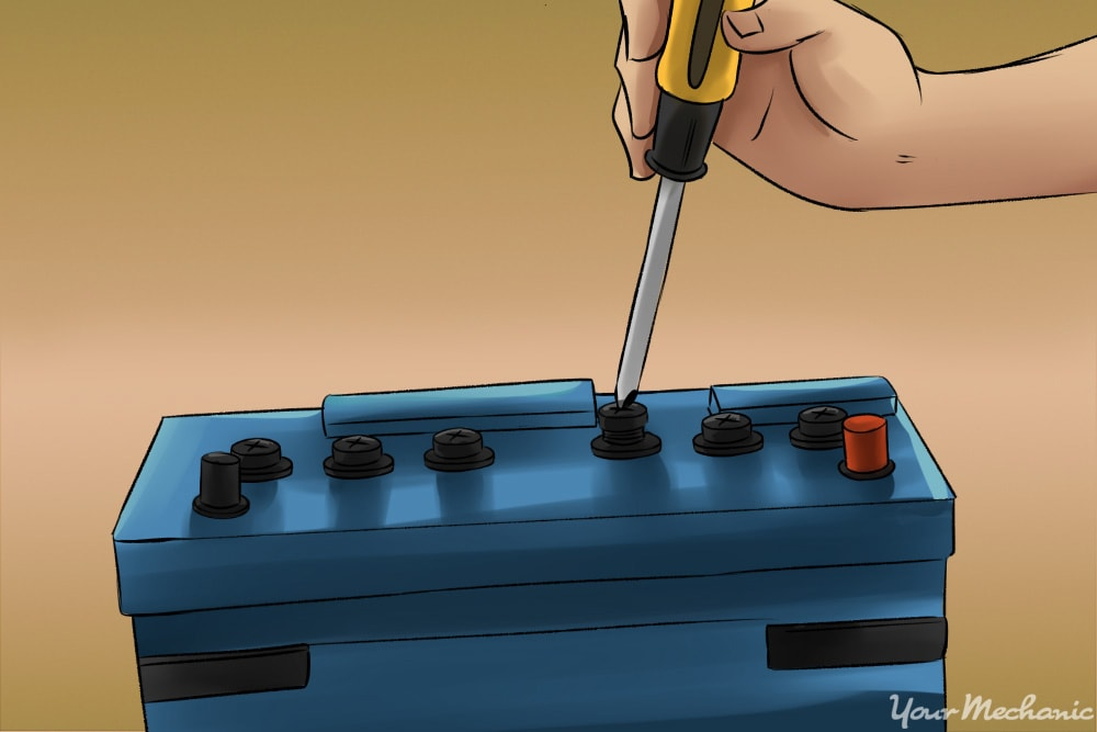 battery caps being removed with a screwdriver