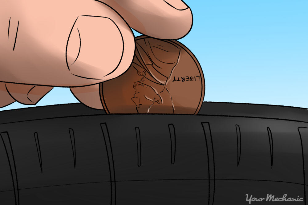 person putting a penny in tire tread