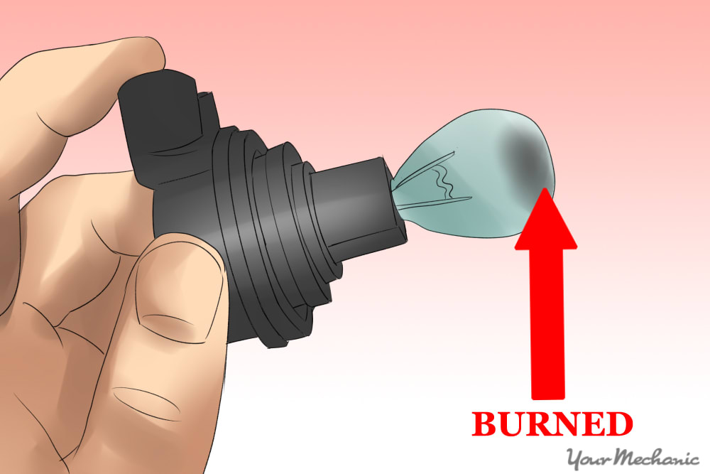 fingers holding onto burnt out bulb