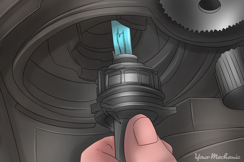 person installing a headlight bulb