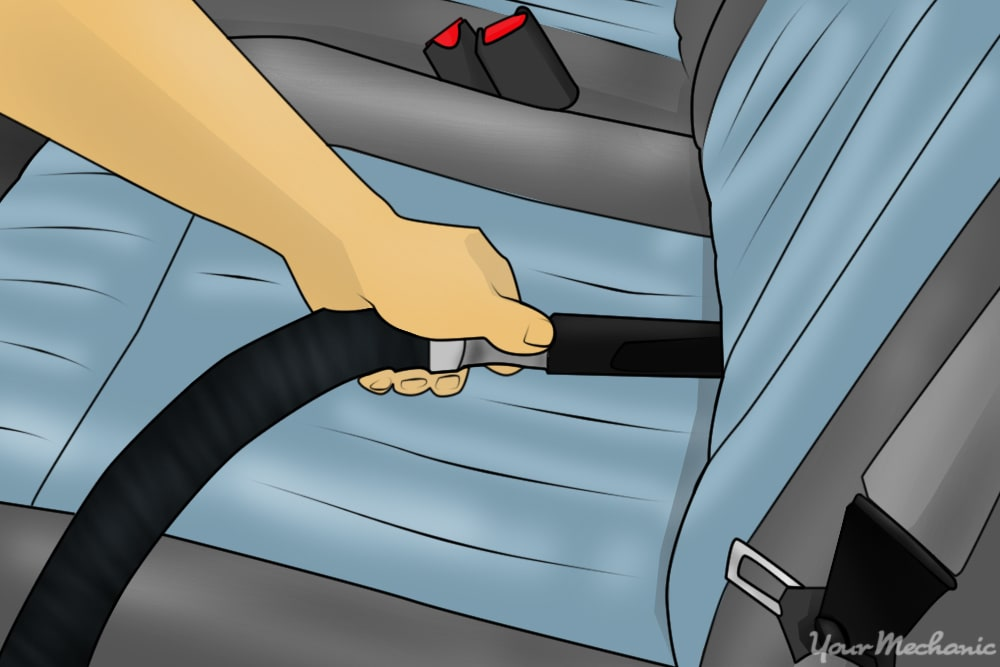 person using crevice tool in between seat back