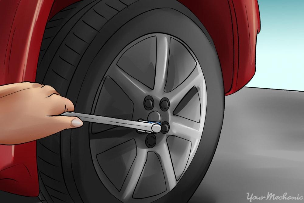 breaker bar loosening a lug nut on a tire