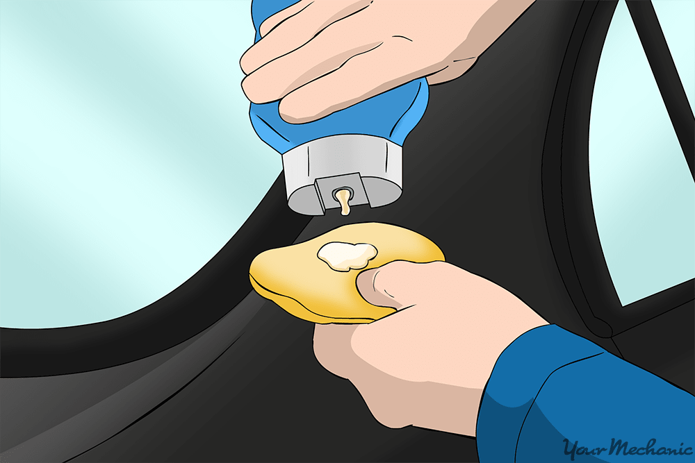 person applying cleaner wax to an applicator