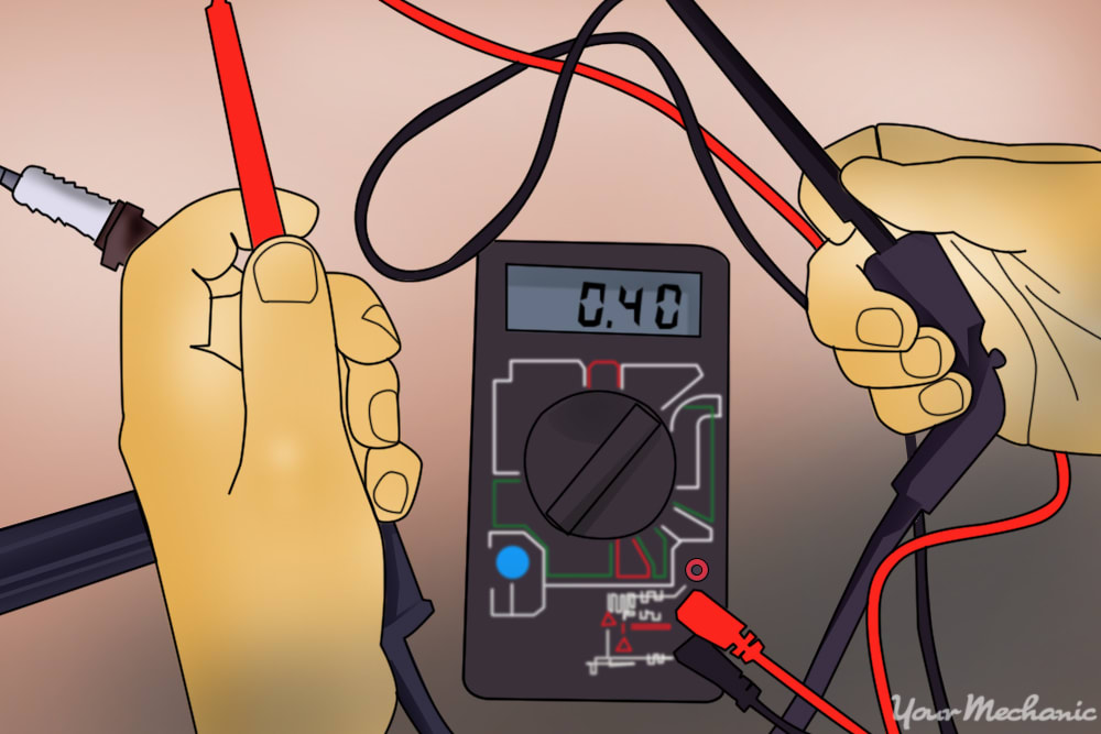 person testing a spark plug wire using a digital multimeter