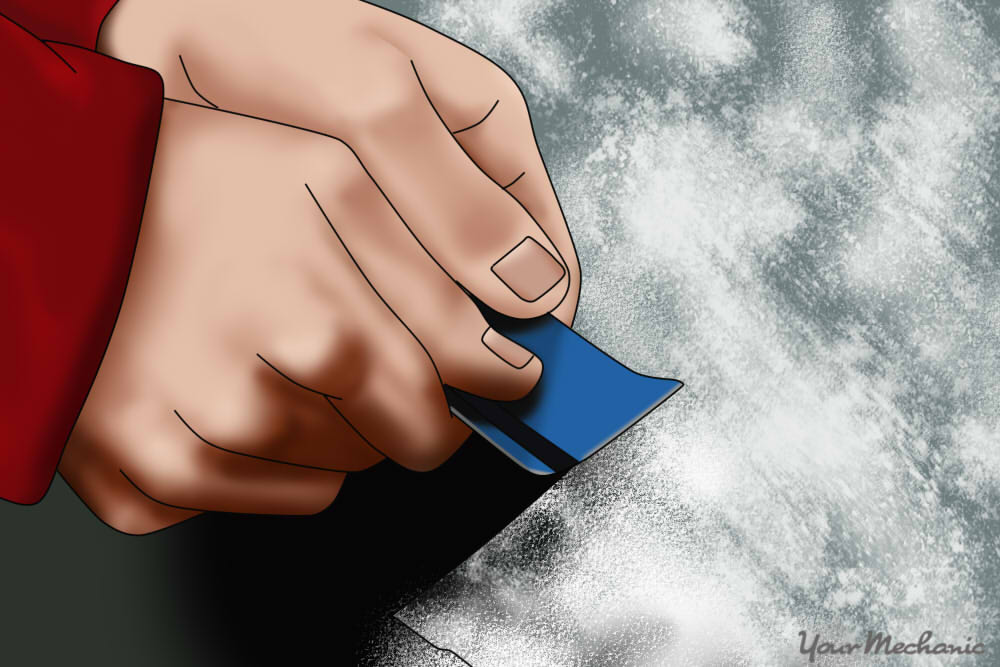 hand using credit card to scrape away a window frost