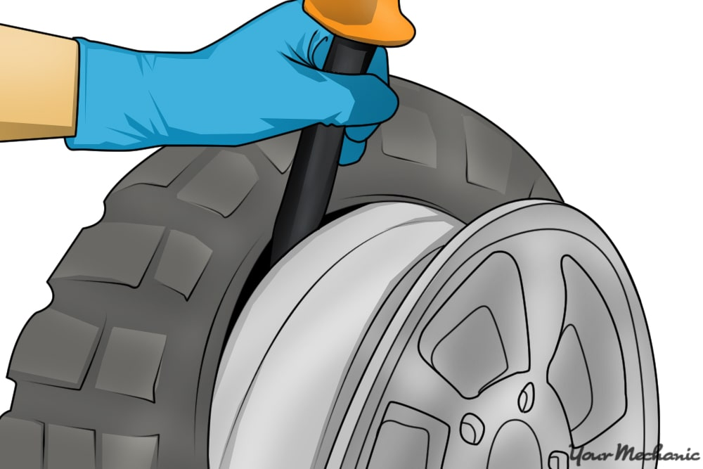 person removing bottom bead of tire iron