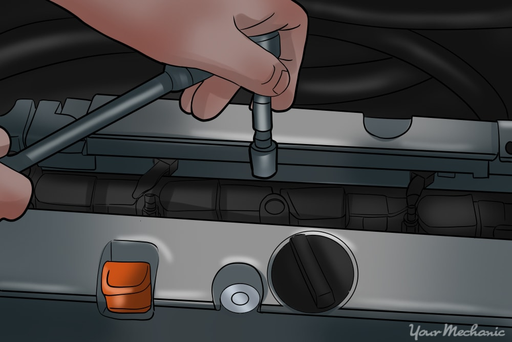 an ignition coil bolt being removed from an engine