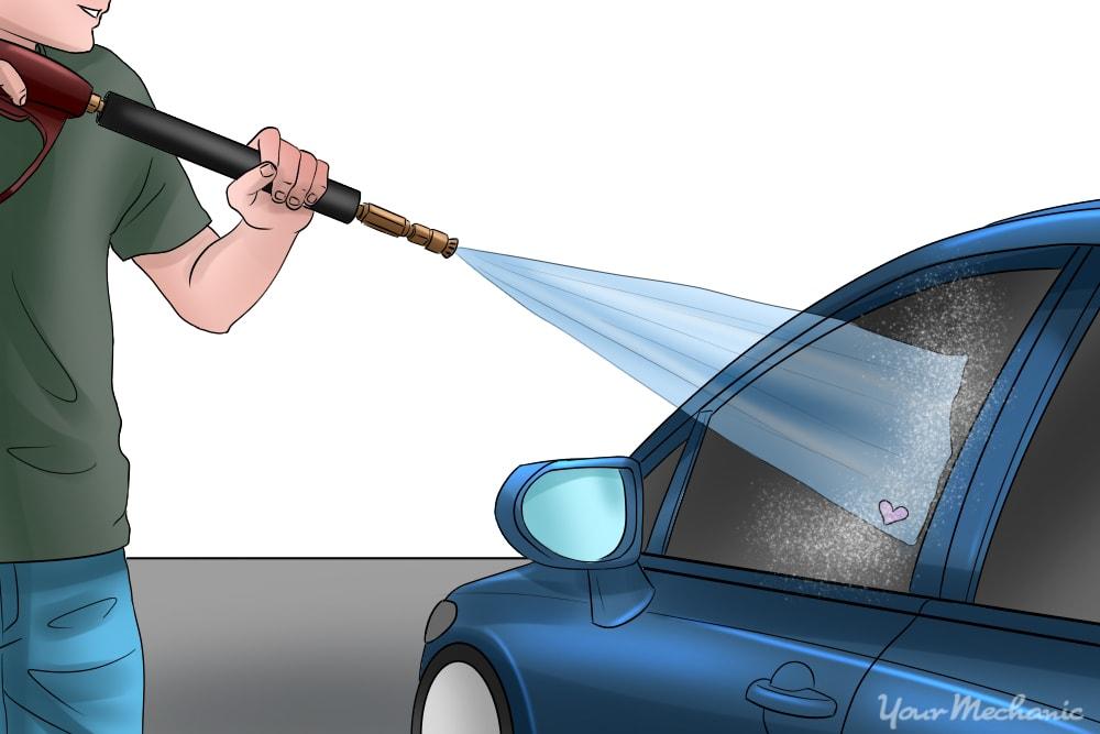 man spraying window with pressure washer