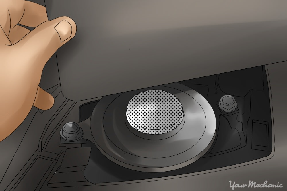 person removing top dash panel to expose speaker