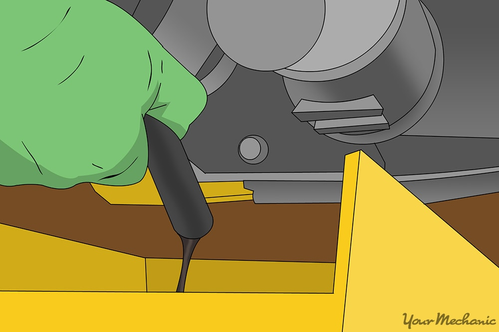 mechanic draining oil hose into drain pan