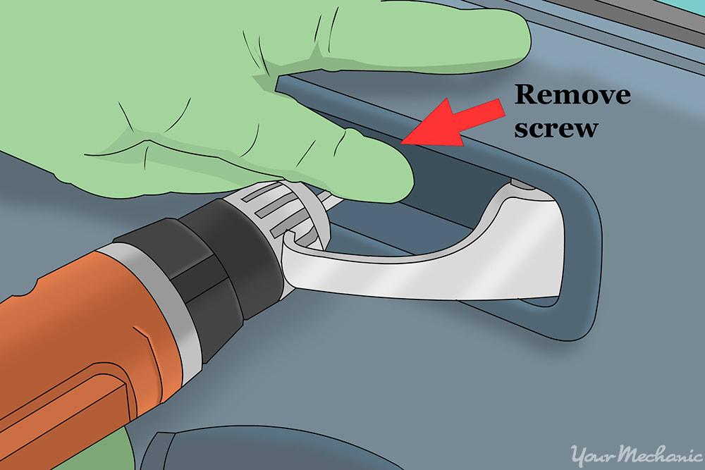 hand removing the screws behind the door handle