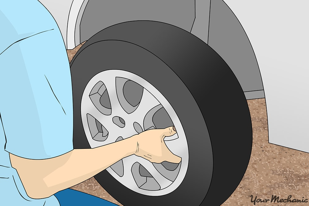 mechanic removing wheel from vehicle
