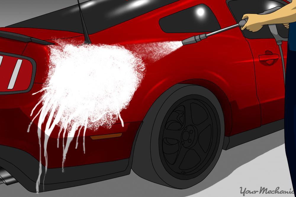 man applying detergent to car