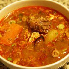 """מרק קוריאני חריף עם בשר בקר וירקות, """"יוקג'אן"""", בתוספת אורז."""