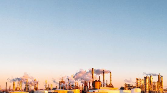 Factory smoke below blue sky